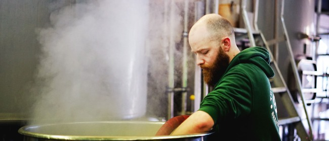 A brewer transferring liquid at The Five Points Brewing Company