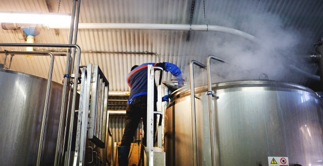 A brewer adds hops of the kettle at the Five Points Brewery in Hackney, London