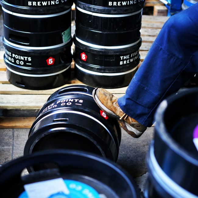 A brewer rolls a keg of Five Points beer in the brewer in Hackney