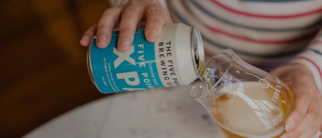 A woman pouring a can of Five Points XPA into a tulip glass