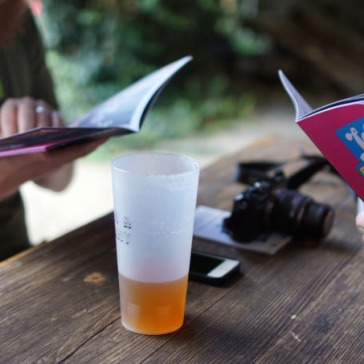 Two people reading London Beer City programmes with a half-drunk pint of beer and a camera on the table