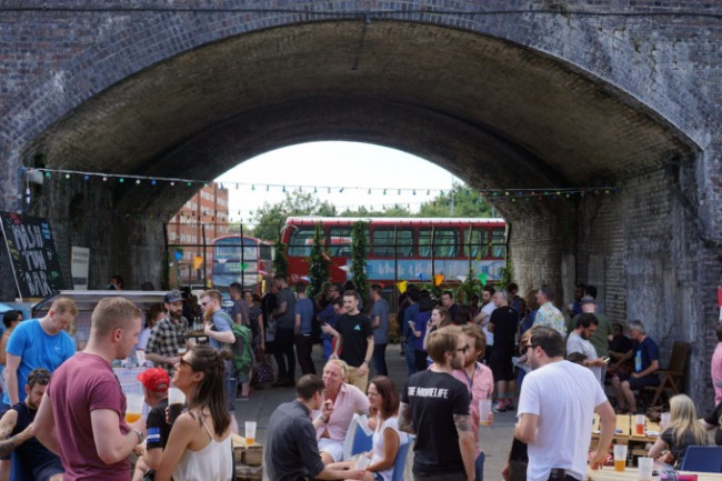 People drinking in the arches next to The Five Points Brewing Company warehouse in Hackney